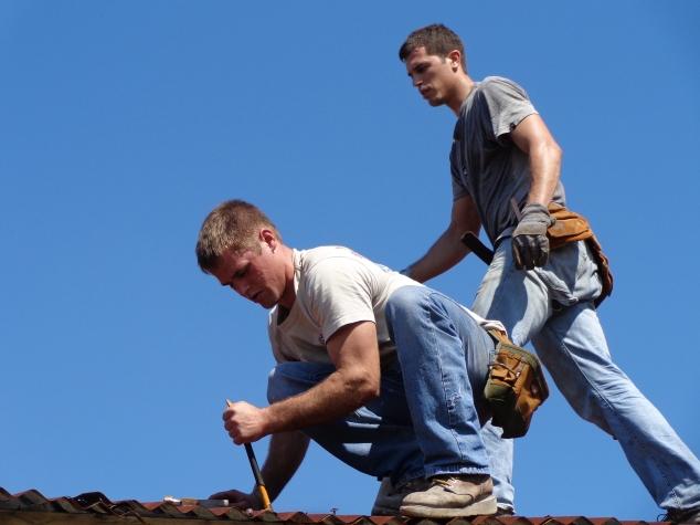 Darin Fiechter and Brian Wagenbach taking tin off roof